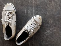 Chaussures blanches sales et vieilles sur l'au sol sale de ciment Photos libres de droits