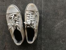 Chaussures blanches sales et vieilles sur l'au sol sale de ciment Images libres de droits