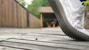 Chaussures blanches se tenant sur le fond en bois foncé de plancher dehors Hippie ou concept occasionnel clips vidéos