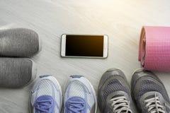 Chaussures bleu, gris et pourpre de sport, tapis de yoga, image libre de droits
