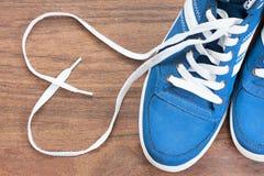 Chaussures bleues avec la dentelle non liée sous forme de coeur sur un plancher en bois Photographie stock libre de droits