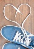 Chaussures bleues avec la dentelle non liée sous forme de coeur sur un plancher en bois Photo libre de droits
