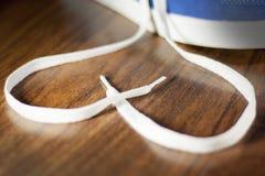 Chaussures bleues avec la dentelle non liée sous forme de coeur sur un plancher en bois Image stock