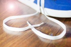 Chaussures bleues avec la dentelle non liée sous forme de coeur sur un plancher en bois Photos libres de droits