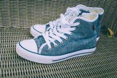 Chaussures bleues d'espadrille de denim sur la chaise en osier Images stock