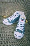 Chaussures bleues d'espadrille de denim sur la chaise en osier Images libres de droits