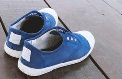 Chaussures bleues d'espadrille de plan rapproché sur le plancher en bois Image stock