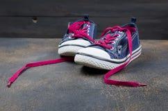 Chaussures bleues de sports avec les dentelles roses sur le plancher Photos libres de droits