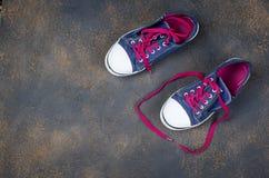 Chaussures bleues de sports avec les dentelles roses sur le plancher Photos stock