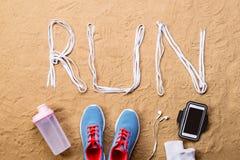Chaussures bleues de sports, bouteille, smartphone contre le sable, tir de studio Photos libres de droits