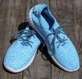 Chaussures bleues de textile sur une surface en bois grise Photo libre de droits