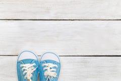 Chaussures bleues du ` s d'enfants sur un fond en bois blanc Configuration plate Photo stock