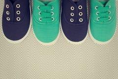 Chaussures bleues et vertes sur le fond avec des zigzags Photos stock