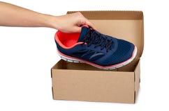 Chaussures bleues femelles de sport avec la boîte et la main d'isolement sur le fond blanc Images libres de droits