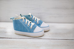 Chaussures bleues pour le bébé garçon sur un fond en bois Photos libres de droits
