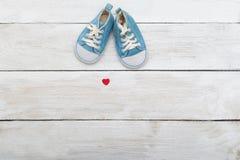Chaussures bleues pour un petit bébé sur un fond en bois Vue d'ab Photos stock