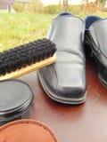 Chaussures brillantes noires avec le cirage à chaussures, une brosse et des dentelles image stock