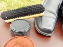 Chaussures brillantes noires avec le cirage à chaussures, une brosse et des dentelles photos libres de droits