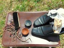 Chaussures brillantes noires avec le cirage à chaussures, une brosse et des dentelles photographie stock libre de droits