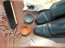 Chaussures brillantes noires avec le cirage à chaussures, une brosse et des dentelles images stock