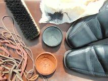 Chaussures brillantes noires avec le cirage à chaussures, une brosse et des dentelles photographie stock