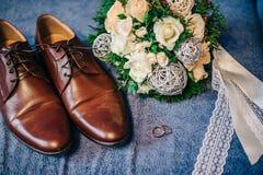 Chaussures brun clair d'été pour le marié avec un bouquet des fleurs Photographie stock
