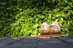 Chaussures brunes d'enfants sur un plancher avec le fond de feuilles dans la soirée ensoleillée Photo libre de droits