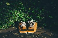 Chaussures brunes d'enfants sur un plancher avec le fond de feuilles dans la soirée ensoleillée Photographie stock libre de droits