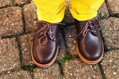 Chaussures brunes de mode sur les pieds de l'enfant Photos stock