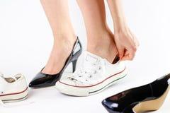 Chaussures changeantes de fille Enlève les chaussures noires et utilise l'espadrille blanche Photo stock