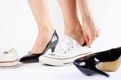 Chaussures changeantes de fille Enlève les chaussures noires et utilise l'espadrille blanche Images stock