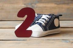 Chaussures colorées d'enfant en bas âge sur le fond en bois Photographie stock