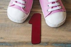 Chaussures colorées d'enfant en bas âge sur le fond en bois Photographie stock libre de droits
