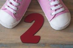 Chaussures colorées d'enfant en bas âge sur le fond en bois Photo stock