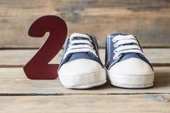 Chaussures colorées d'enfant en bas âge sur le fond en bois Image stock