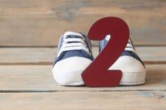 Chaussures colorées d'enfant en bas âge sur le fond en bois Photos libres de droits
