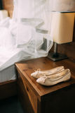 Chaussures crèmes de la jeune mariée sur le vert sur une table en bois de table Photo stock