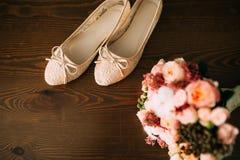 Chaussures crèmes de la jeune mariée sur le vert sur une table en bois de table Images stock
