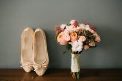 Chaussures crèmes de la jeune mariée sur le vert sur une table en bois de table Photographie stock