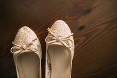Chaussures crèmes de la jeune mariée sur le vert sur une table en bois de table Photo libre de droits