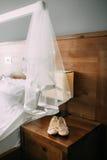 Chaussures crèmes de la jeune mariée sur le vert sur une table en bois de table Photographie stock libre de droits