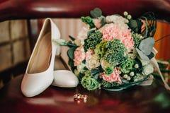 Chaussures croisées du ` s de jeune mariée avec un bouquet avec des anneaux Photo stock