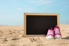 Chaussures d'enfant en bas âge et mini panneau de craie sur le sable, Ba de concept de plage Photos stock