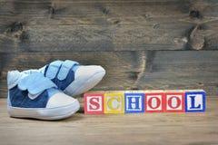 Chaussures d'enfant et école de mot Photographie stock