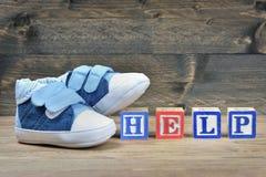 Chaussures d'enfant et aide de mot Photographie stock