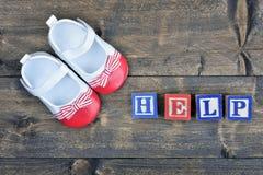 Chaussures d'enfant et aide de mot Photographie stock libre de droits
