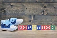 Chaussures d'enfant et solution de mot Photographie stock libre de droits