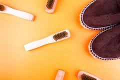 Chaussures d'espadrille de suède de Brown avec des brosses sur le fond de papier jaune Photos stock