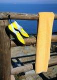 Chaussures d'essuie-main et de plage sur la frontière de sécurité en bois Photo libre de droits