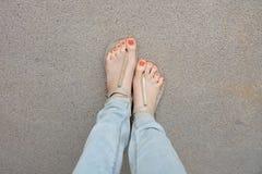 Chaussures d'or et x28 ; Slippers& x29 ; sur des jambes et des pieds de fille au sol Images stock